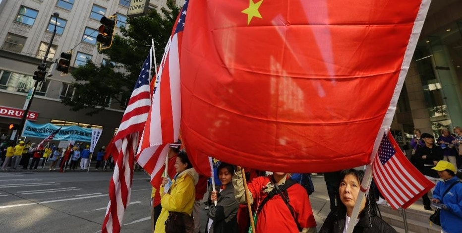 People hold Chinese and American flags as they stand near the hotel where Chinese President Xi Jinping is staying Tuesday, Sept. 22, 2015, in Seattle. Xi was in Seattle on his way to Washington for a White House state dinner on Friday. (AP Photo/Ted S. Warren)