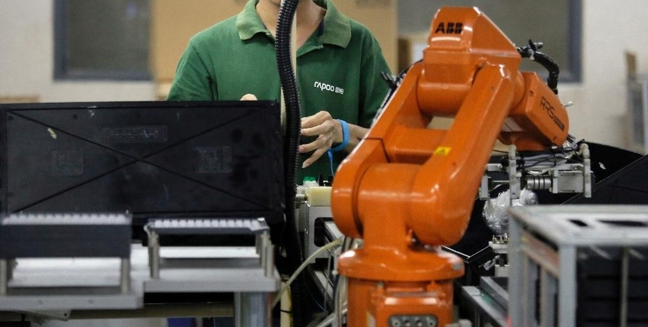 In this Aug. 21, 2015 photo, a Chinese man works next to an orange robot arm at Rapoo Technology factory in southern Chinese industrial boomtown of Shenzhen. Factories in China are rapidly replacing those workers with automation, a pivot that's encouraged by rising wages and new official directives aimed at helping the country move away from low-cost manufacturing as the supply of young, pliant workers shrinks.  (AP Photo/Vincent Yu)