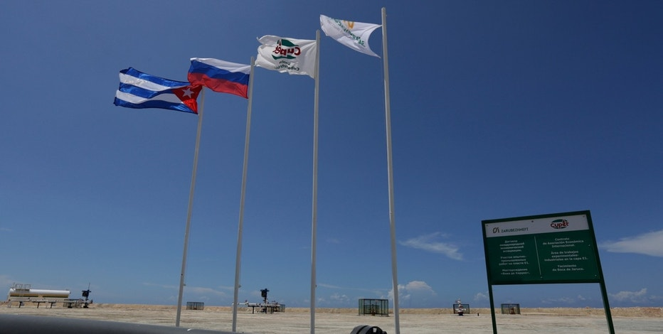 The national flags of Russia and Cuba, alongside the flags of Russian oil company Zarubezhneft and Cuban oil company Cupet, are seen near a sign designating the joint development project of the oil companies, on the outskirts of Havana.