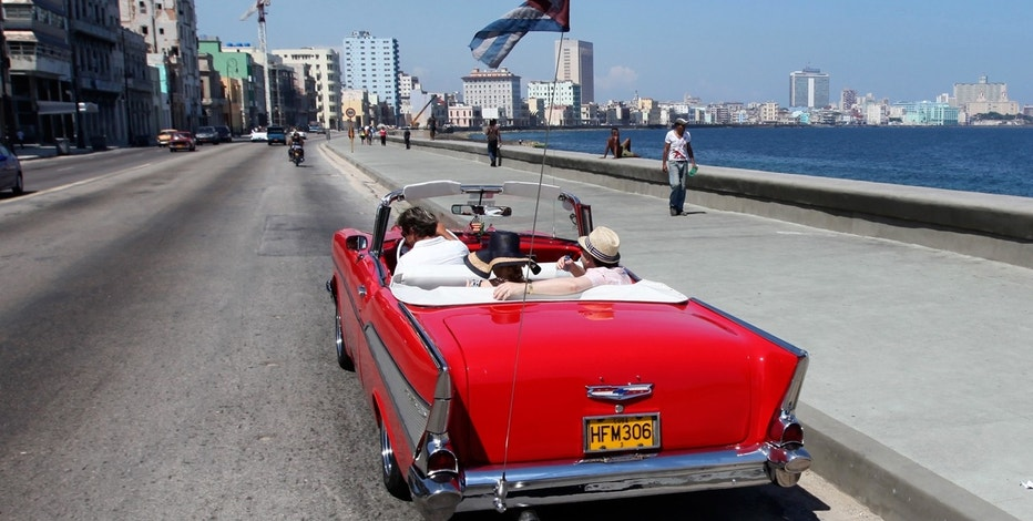 Tourists ride a U.S.-made 1957 Chevrolet Bel-Air convertible car on Havana's seafront boulevard 'El Malecon'.