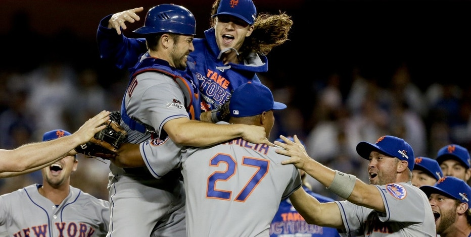 New York Mets starting pitcher Jacob deGrom, above right, catcher Travis d'Arnaud, left, and other Mets players celebrate a 3-2 win over the Los Angeles Dodgers in Game 5 of baseball's National League Division Series on Thursday, Oct. 15, 2015, in Los Angeles.
