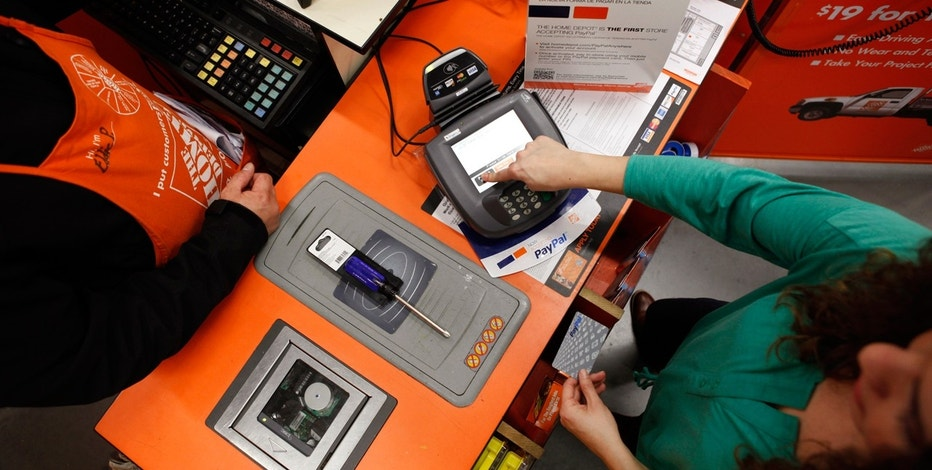 A Home Depot employee and a public relations representative demonstrate how the PayPal card works at a cashier station at a Home Depot store.