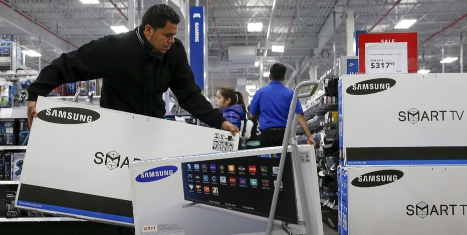 A shopper puts televisions on a shopping cart  at a Best Buy store in Westbury, New York November 27, 2015. Crowds were thin at U.S. stores and shopping malls in the early hours of Friday, initial spot checks showed, as shoppers responded to early Black Friday discounts with a mix of enthusiasm and caution. REUTERS/Shannon Stapleton - RTX1W4B2