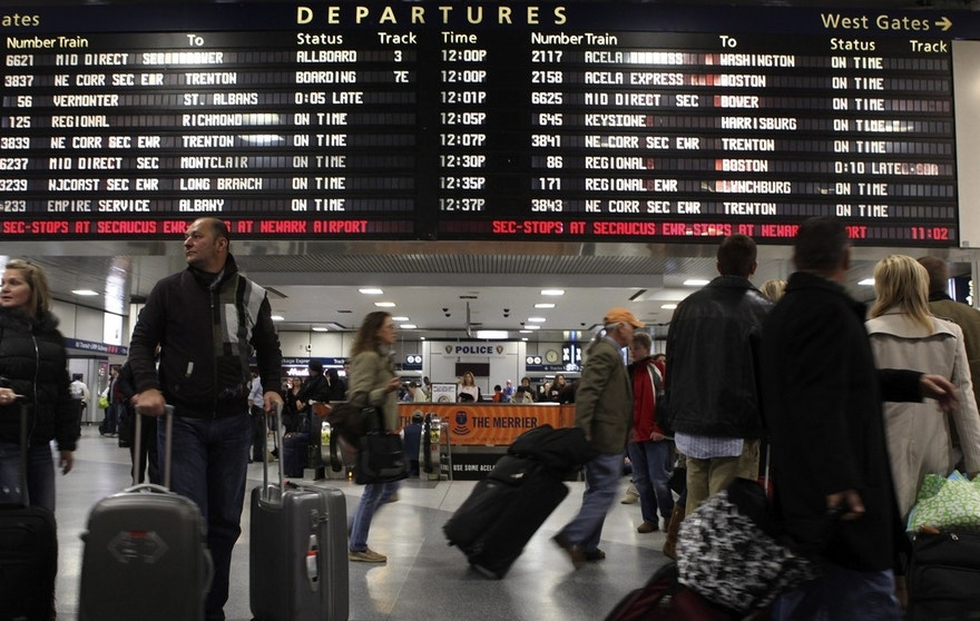 Travelers walk in front of an Amtrak departure board at Penn Station