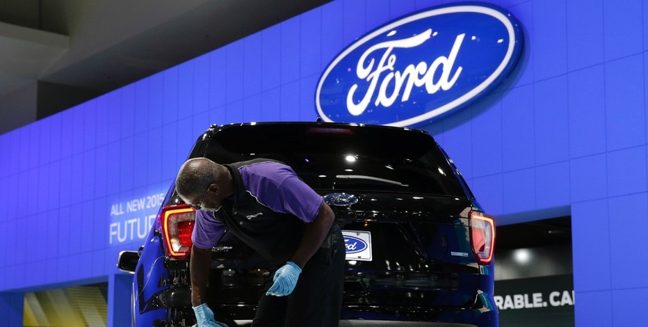 An auto detailer dusts a 2016 Ford Explorer at the press day for the Washington Auto Show in Washington, January 22, 2015.