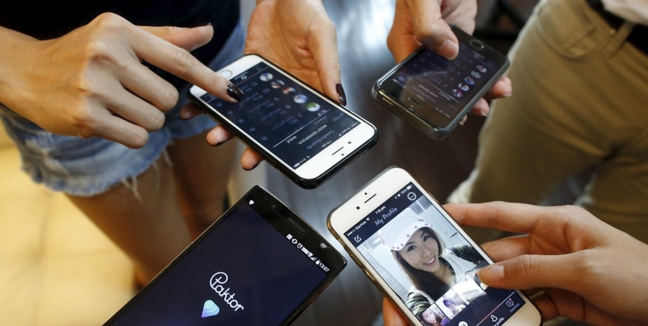 Developers of smartphone dating app Paktor log in to their accounts to show their Paktor profiles at their office in Singapore July 16, 2015. Homegrown apps hope their understanding of local cultural norms will give them a leg up over global rivals such as U.S-based Tinder, which has millions more users but which is seen as conduit for finding sexual partners, as well as friends. REUTERS/Edgar Su - RTX1KLOD