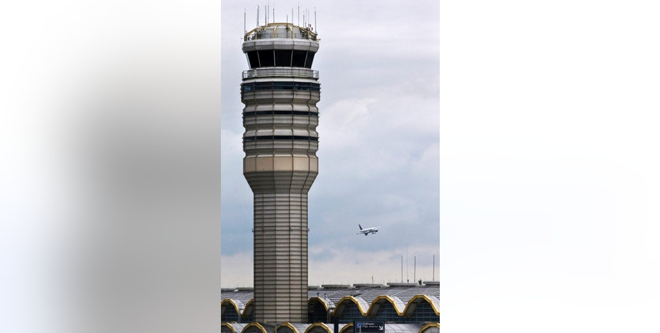 An airplane flies past the air traffic control tower at Washington's Ronald Reagan National Airport, Monday, Aug. 10, 2015. For more than three years, the government has kept secret a study it requested that found air traffic controllers' work schedules often lead to chronic fatigue, making them less alert and endangering the safety of the national air traffic system, according to report on the study obtained by The Associated Press. (AP Photo/Jacquelyn Martin)