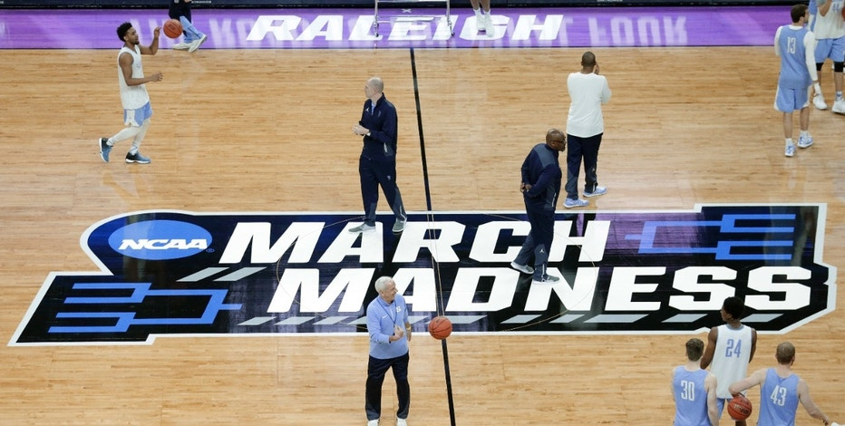 North Carolina head coach Roy Williams, center, passes a ball to players during practice for a first-round men's college basketball game in the NCAA Tournament in Raleigh, N.C., Wednesday, March 16, 2016. North Carolina plays Florida Gulf Coast on Thursday. (AP Photo/Chuck Burton)