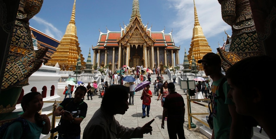 Tourists visit the Grand Palace in Bangkok May 24, 2014. The Thai army's imposition of martial law is another blow to the country's tourist industry, adding to the economic pain from six months of destabilizing street protests as airlines cut back on flights and concern over insurance adds to travelers' worries. Tourism officials put a brave face on the latest twist in the long-running civil strife, saying it was too early to gauge the impact on tourist arrivals, which already dipped nearly 6 percent in the first three months of the year. REUTERS/Erik De Castro (THAILAND - Tags: POLITICS TRAVEL CIVIL UNREST BUSINESS) - RTR3QMFB