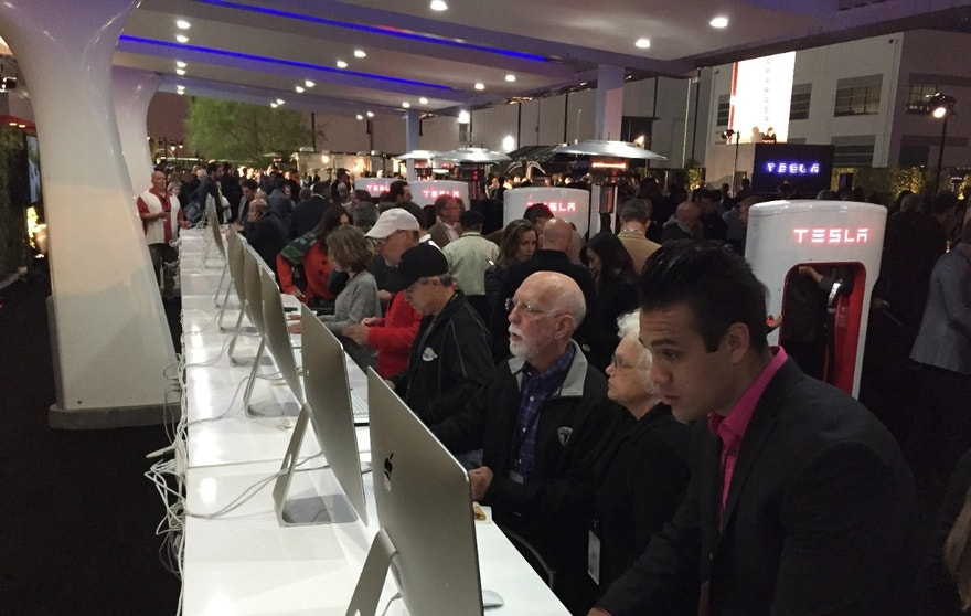 People sit at computers where they can reserve one of the cars before Tesla Motors unveils the Model 3 at the Tesla Motors design studio Thursday, March 31, 2016, in Hawthorne, Calif.