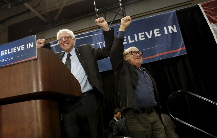U.S. Democratic presidential candidate Bernie Sanders and actor Danny DeVito gesture during a rally.