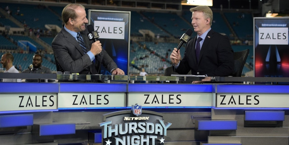 """FILE - In this Nov. 19, 2015, file photo, Thursday Night Football sportscasters Bill Cowher, left, and Phil Simms broadcast from the set on the field before an NFL football game between the Jacksonville Jaguars and the Tennessee Titans in Jacksonville, Fla. The NFL has picked Twitter to stream its Thursday night games. When the league negotiated its latest deal for Thursdays, it decided to sell the streaming rights separately for an """"over the top"""" broadcast.  (AP Photo/Phelan M. Ebenhack, File)"""