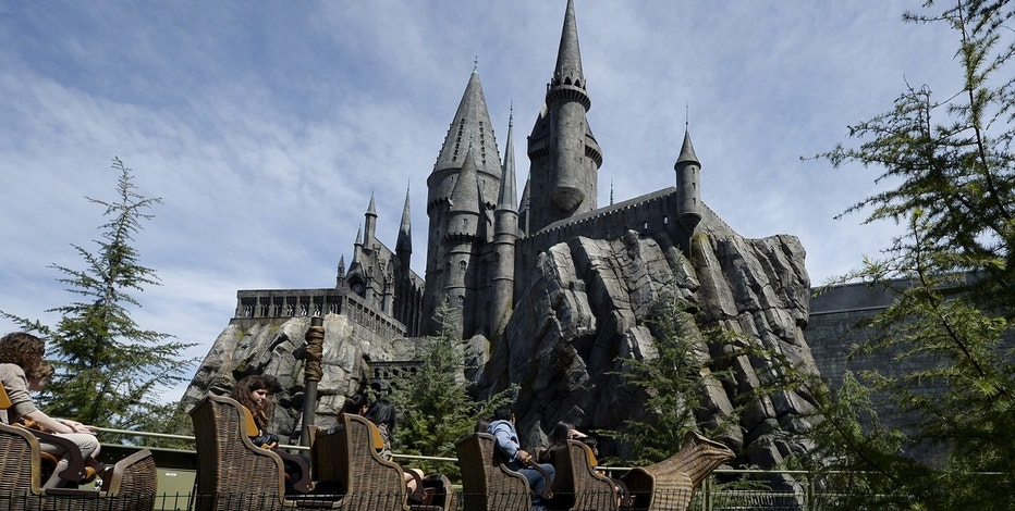 Guests take a ride on a rollercoaster outside the Hogwarts School at The Wizarding World of Harry Potter theme park at the Universal Studios Hollywood in Los Angeles.