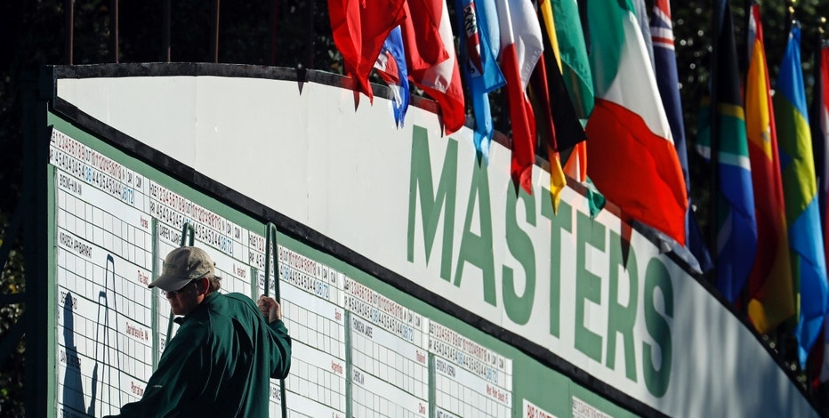 A scorekeeper places numbers on a leaderboard during the first round of the Masters golf tournament Thursday, April 7, 2016, in Augusta, Ga.