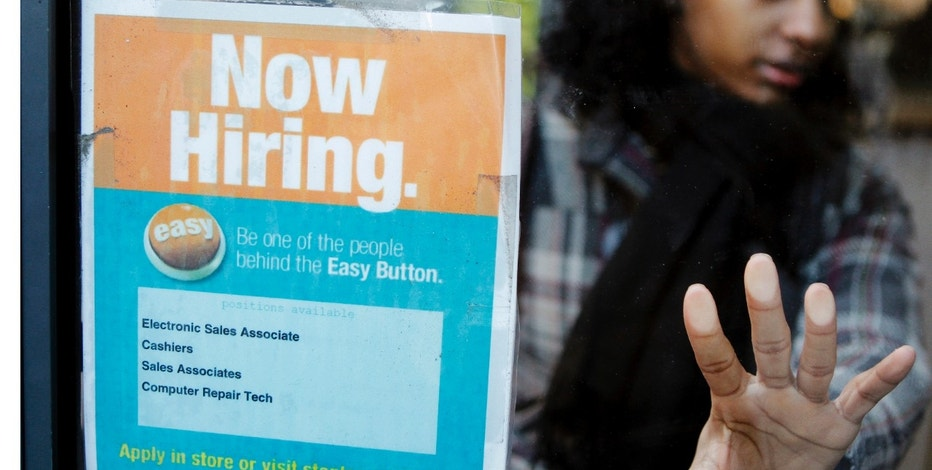 """A woman opens a glass door with a """"Now Hiring"""" sign on it as she enters a Staples store in New York March 3, 2011.  New U.S. claims for unemployment benefits fell last week to their lowest level in more than 2-1/2 years, signalling an acceleration in job creation could be taking shape.   REUTERS/Lucas Jackson (UNITED STATES - Tags: EMPLOYMENT BUSINESS)"""