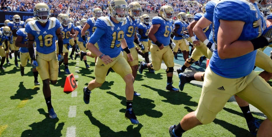 FILE - In this Sept. 5, 2015, file photo, UCLA players run onto the field for an NCAA college football game against Virginia at Rose Bowl in Pasadena, Calif. UCLA and Under Armour have agreed to an athletic shoe and apparel deal that will pay the school a record $280 million over 15 years, in a deal that was announced Tuesday, May 24, 2016.  (AP Photo/Jae C. Hong)