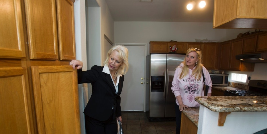 Fafie Moore (L), a Reality Executives owner/broker, and realtor Helen Riley look at kitchen cabinets of a home being offered for sale in Henderson, Nevada April 8, 2013.