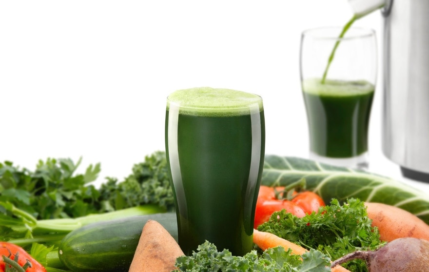 Focus is on the freshly made vegetable juice surrounded by organic vegetables while another juice is being made in the background. Juicing fresh organic vegetables and fruit for healthy living.