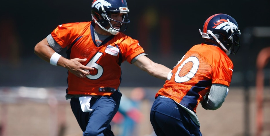 Denver Broncos quarterback Mark Sanchez, left, hands off the ball to rookie running back Devontae Booker during an NFL football practice at the team's headquarters Tuesday, June 7, 2016, in Englewood, Colo.