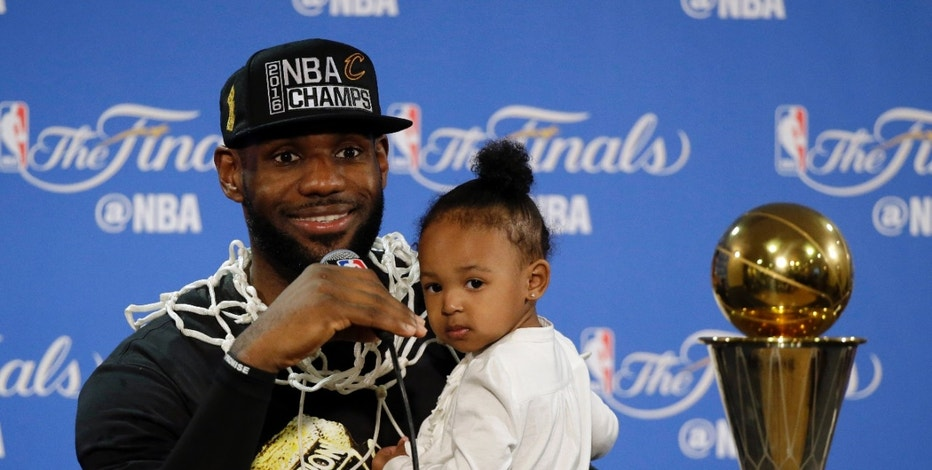 Cleveland Cavaliers' LeBron James answers questions as he holds his daughter Zhuri during a post-game press conference after Game 7 of basketball's NBA Finals Sunday, June 19, 2016, in Oakland, Calif. Cleveland won 93-89. (AP Photo/Eric Risberg)