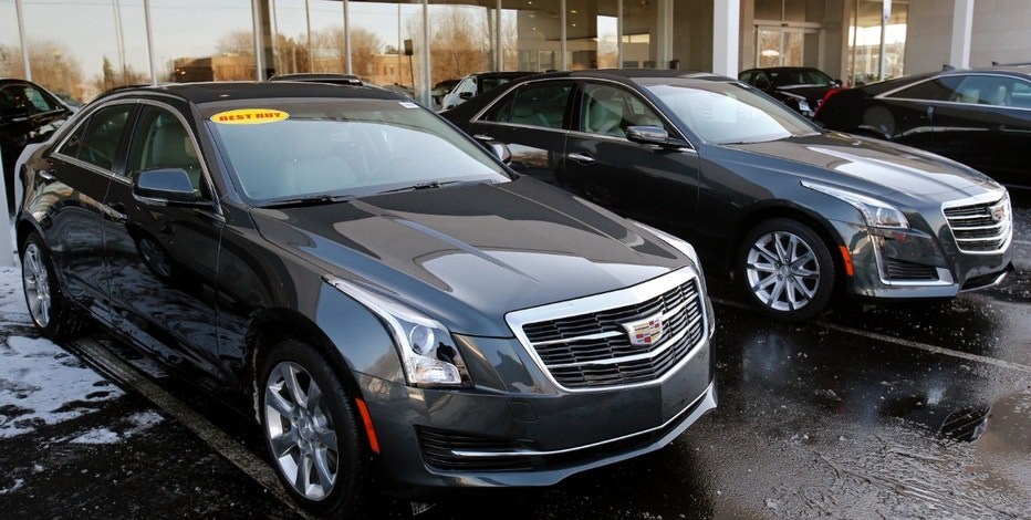 An unsold Cadillac ATS (L) and Cadillac CTS vehicle sit in the front lot of a Cadillac automobile dealership in Plymouth, Michigan, February 5, 2015.