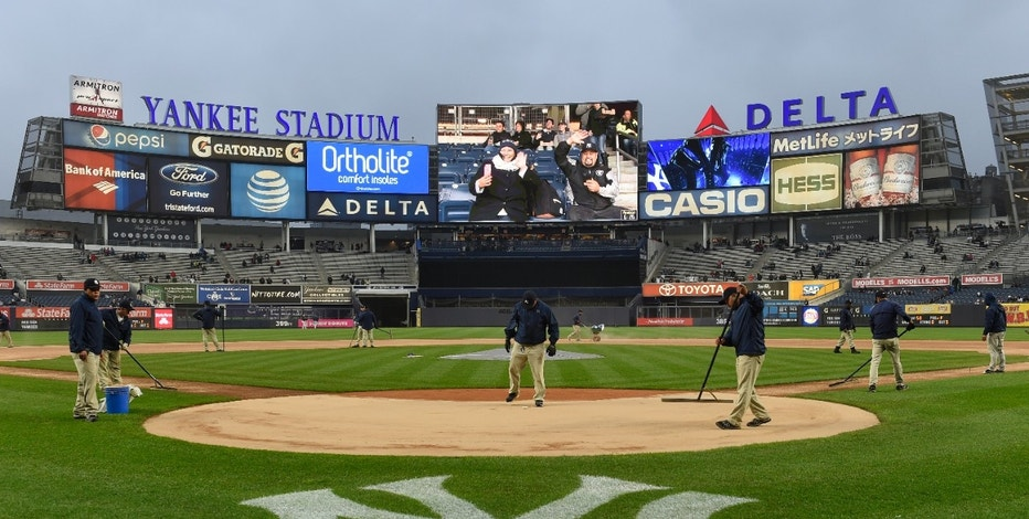 New York Yankees grounds crew prepare the field as intermittent rain falls before a baseball game against the Boston Red Sox at Yankee Stadium, Friday, May 6, 2016, in New York. (AP Photo/Kathy Kmonicek)