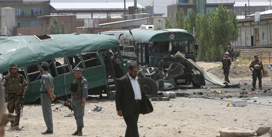 Afghan security forces inspect the site of a suicide attack on the outskirts of Kabul, Afghanistan, Thursday, June 30, 2016. An Afghan official said that a suicide bomber attacked a bus carrying trainee policemen. (AP Photo/Rahmat Gul)
