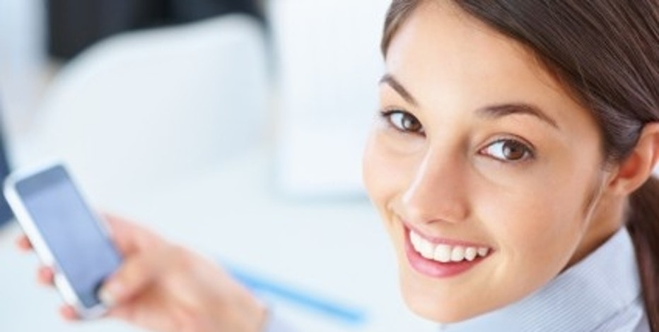 Closeup of female executive using mobile phone and giving you cute smile