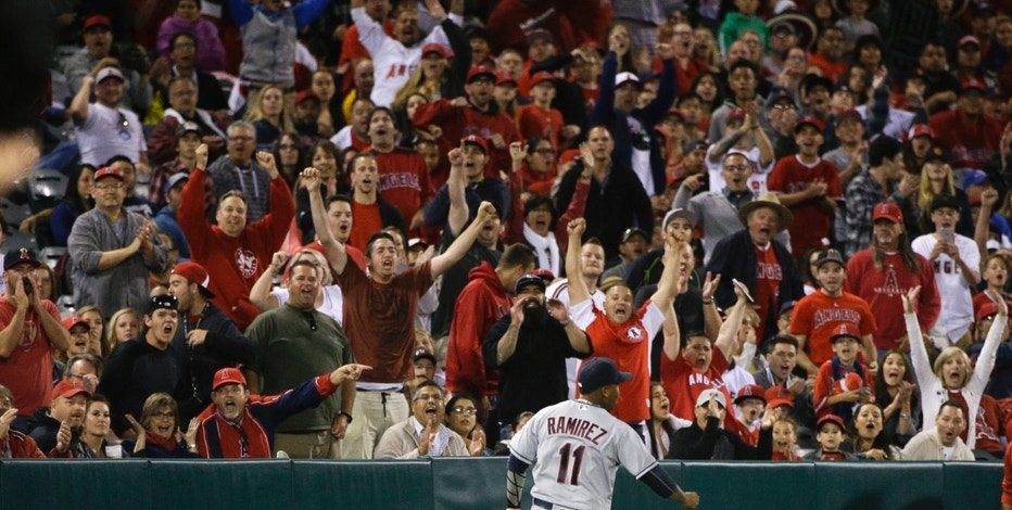 Fans cheer as Cleveland Indians' Jose Ramirez misses a two-run single by Los Angeles Angels' Kole Calhoun during the seventh inning of a baseball game, Saturday, June 11, 2016, in Anaheim, Calif.