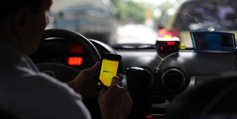A taxi driver checks an app on his smartphone in Rio de Janeiro April 15, 2013. As Brazil rushes to introduce a blazing-fast fourth-generation wireless network before the 2014 World Cup, fewer than a dozen compatible smartphones will be available in stores, compared with the hundreds of models on sale worldwide. Picture taken on April 15, 2013. REUTERS/Ricardo Moraes (BRAZIL - Tags: BUSINESS TELECOMS) - RTXYPNH