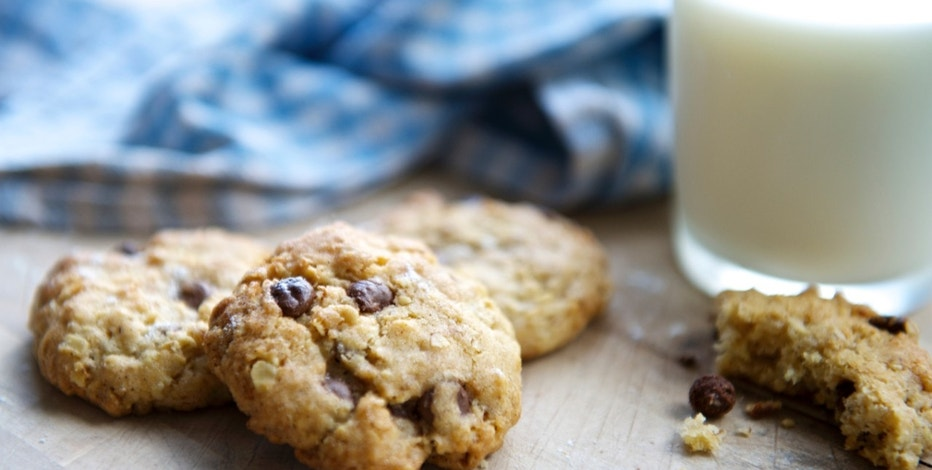 Cork, Ireland - July 28, 2013: Freshly made chocolate chip cookies on a wooden surface beside a glass of milk with crumbs and chocolate chips scattered around.