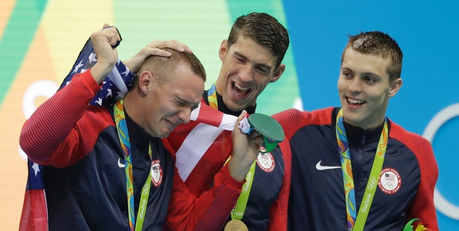 Caeleb Dressel, left, Michael Phelps and Ryan Held, right, from the United States, celebrate after winning the gold medal in the men's 4x100-meter freestyle relay during the swimming competitions at the 2016 Summer Olympics, Sunday, Aug. 7, 2016, in Rio de Janeiro, Brazil. (AP Photo/Matt Slocum)