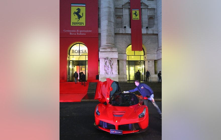 "A staff member cleans ""LaFerrari"" sports car in front of Milan's stock exchange, downtown Milan, Italy January 4, 2016. Ferrari shares opened at 43 euros in their Milan bourse debut on Monday as the luxury sports car maker completed its spin off from parent Fiat Chrysler Automobiles, establishing the Agnelli family as its biggest investor."