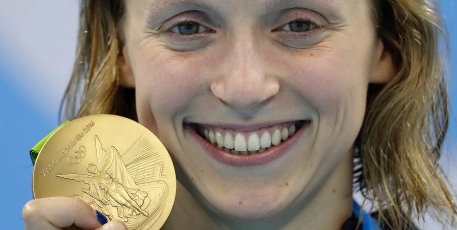 United States' Katie Ledecky shows off her gold medal in the women's 800-meter freestyle medals ceremony during the swimming competitions at the 2016 Summer Olympics, Friday, Aug. 12, 2016, in Rio de Janeiro, Brazil. (AP Photo/Michael Sohn)