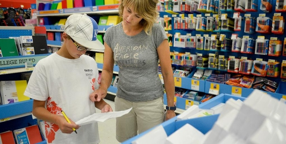 FILE - In this July 30, 2014 file photo, Jill Courtney, right, shops for school supplies for her sons, Will, left, and Reid, not seen, at a Target store in St. Joseph, Mo.  This season, stores have focused even more on offering new services and apps to cater to increasingly time-starved smart-phone, savvy parents to help them save time and money for the annual shopping ritual. (AP Photo/St. Joseph News-Press, Sait Serkan Gurbuz, File)