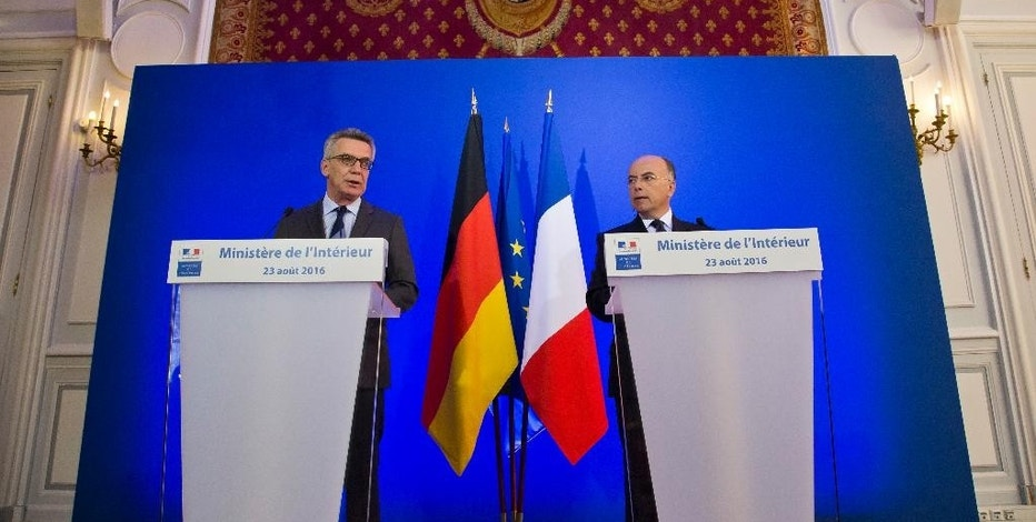 German Interior Minister Thomas de Maiziere, left, and French Interior Minister Bernard Cazeneuve attend a joint media conference in Paris, Tuesday, Aug.23, 2016. The French and German interior ministers said Tuesday they're pushing for a Europe-wide policy limiting encryption, and want it discussed at an EU summit in Slovakia next month. (AP Photo/Michel Euler)