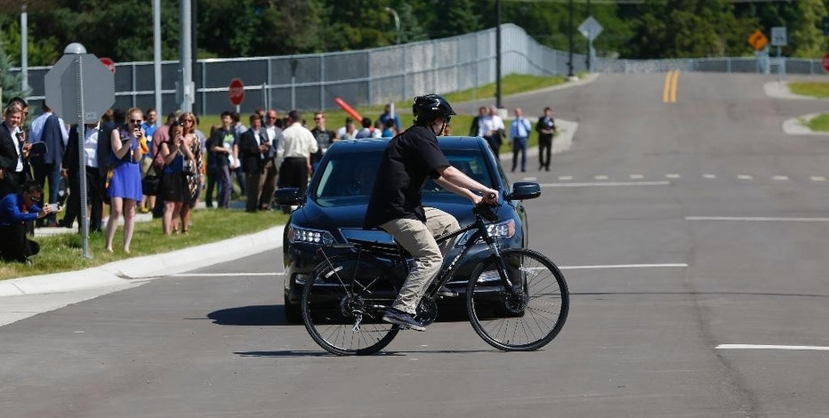 FILE - In this July 20, 2015 file photo, a cyclist crosses in front of a vehicle as part of a demonstration at Mcity on the University of Michigan campus in Ann Arbor, Mich. Automakers say cars that wirelessly talk to each other are finally ready for the road. The cars hold the potential to dramatically reduce traffic deaths, improve the safety of self-driving cars and someday maybe even help solve traffic jams. Government and industry have spent more than a decade and more than $1 billion researching and testing the technology, known as vehicle-to-vehicle communications, or V2V. (AP Photo/Paul Sancya, File)
