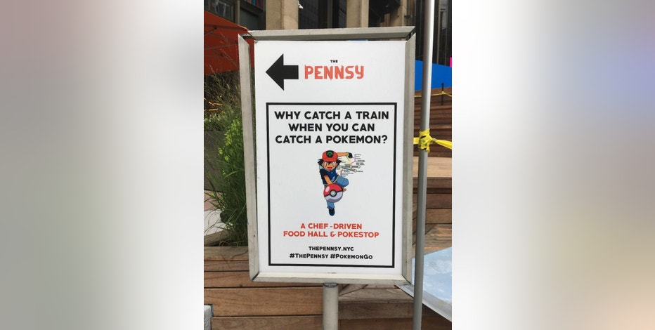 "This Thursday, Aug. 18, 2016, photo shows a sign at The Pennsy food court near New York's Penn Station, urging passersby to catch a Pokemon instead of a train. From doughnut shops to zoos, businesses and organizations are finding creative ways to capitalize on ""Pokemon Go."" (AP Photo/Anick Jesdanun)"