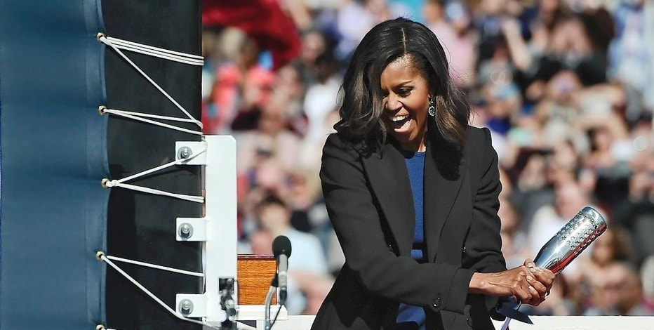 FILE - In this Oct. 10, 2015 file photo, first lady Michelle Obama christens the USS Illinois with a bottle of sparkling wine at Electric Boat, a division of General Dynamics, shipyard in Groton, Conn. The submarine will officially join the U.S. Navy fleet in a fall 2016 ceremony. (AP Photo/Jessica Hill, File)