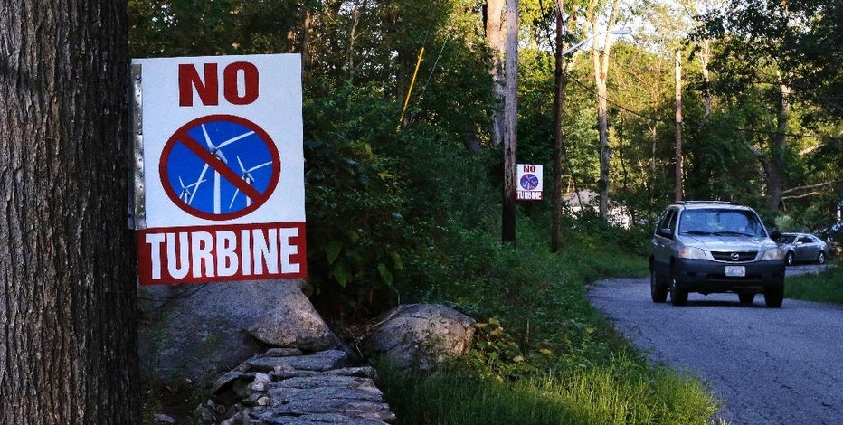 In this Thursday, Aug. 25, 2016 photo, a car passes signs against a proposed wind turbine hanging from a neighborhood telephone pole and tree, in North Smithfield, R.I. Even as Rhode Island makes history as the first U.S. state with an offshore wind farm, its people are not so fond of wind turbines sprouting up on land near where they live. Town leaders in North Smithfield are proposing a ban on any new wind turbines in the rural community, though it might be too late to stop a turbine that Ruth Pacheco has a permit to build on her 52-acre farm property there. (AP Photo/Charles Krupa)