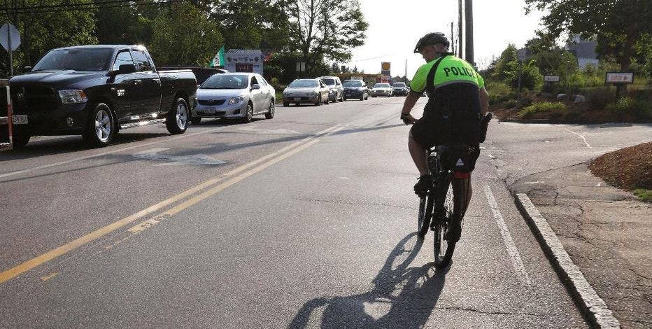 In this July 20, 2016 photo, police officer Matthew Monteiro watches for motorists who may be texting while patrolling on his bicycle during afternoon rush hour in East Bridgewater, Mass. Efforts to discourage drivers from texting have increased in recent years, but the consensus is that the problem is only getting worse. Police departments around the country have gotten creative in trying to get drivers to put down their phones. (AP Photo/Steven Senne)