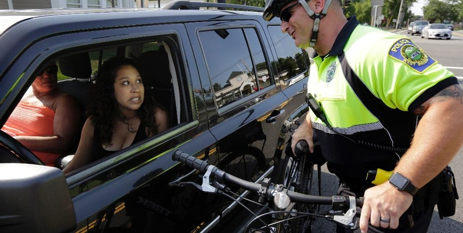 In this July 20, 2016 photo, police officer Matthew Monteiro speaks to a motorist about texting while driving while patrolling on his bicycle in East Bridgewater, Mass. Efforts to discourage drivers from texting have increased in recent years, but the consensus is that the problem is only getting worse. Police departments around the country have gotten creative in trying to get drivers to put down their phones. (AP Photo/Steven Senne)
