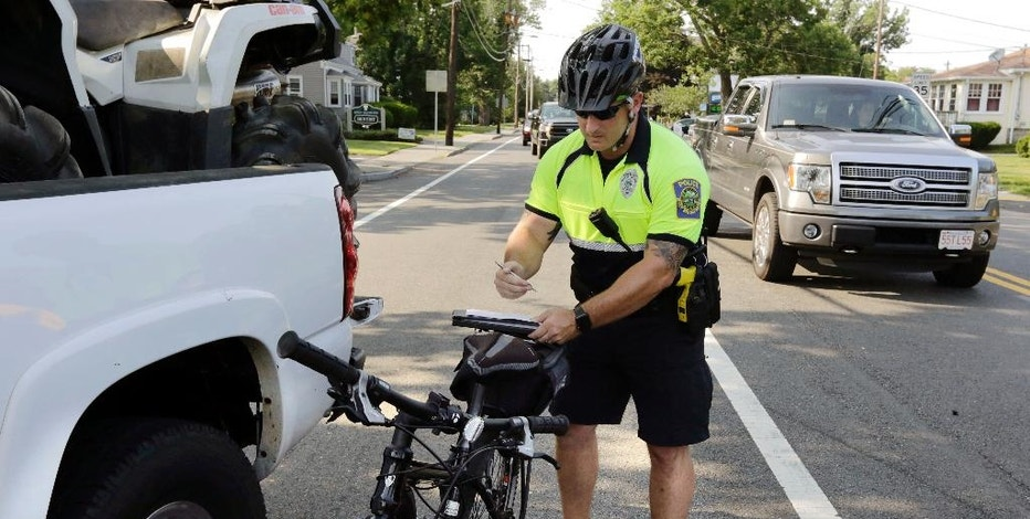 In this Wednesday, July 20, 2016 photo, police officer Matthew Monteiro writes a citation for a motorist who was texting while driving, after pulling the vehicle over while patrolling on his bicycle in East Bridgewater, Mass. Efforts to discourage drivers from texting have increased in recent years, but the consensus is that the problem is only getting worse. Police departments around the country have gotten creative in trying to get drivers to put down their phones. (AP Photo/Steven Senne)