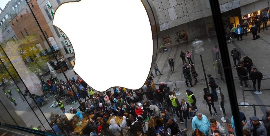 FILE - In this Friday, Sept. 25, 2015, file photo, people wait in front of an Apple store in Munich, before the worldwide launch of the iPhone 6s. After a tax ruling against Apple on Tuesday, Aug. 30, 2016, the spotlight turns to dozens of companies that have boosted earnings taking advantage of low tax rates abroad. (AP Photo/Matthias Schrader, File)