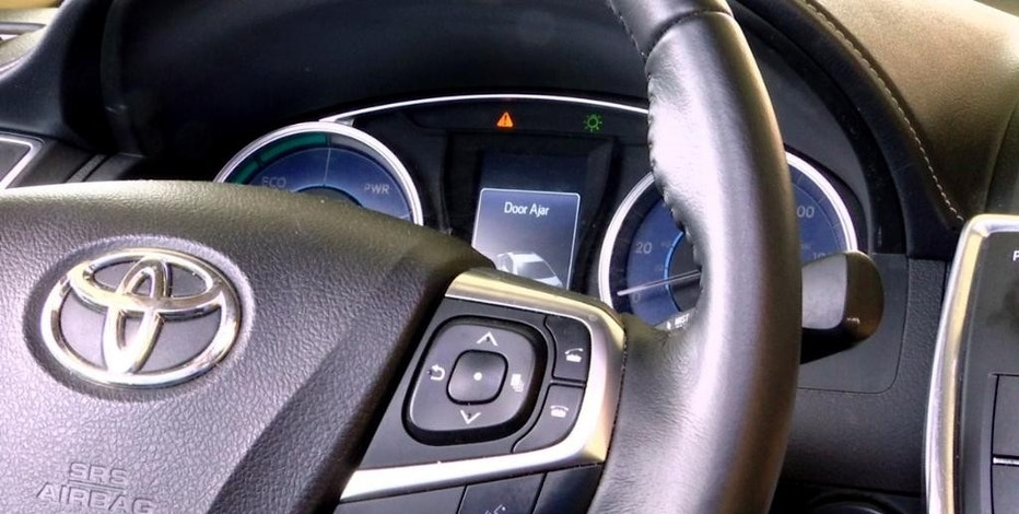 In this Aug. 16, 2016, image taken from video, the dashboard of a Toyota sedan in York Township, Mich., displays a warning icon informing the driver that a door is ajar. The indicator is accompanied by an audio alert. As more features have been added in cars and trucks, the number of sounds has grown, and their functions have become more important. Nearly all automakers have engineers and others assigned to special groups that make sure musical greeting sounds are pleasant and that warnings are so annoying they get a driver's attention fast. (AP Photo/Mike Householder)