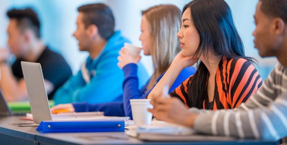 A multi-ethnic group of college age students are sitting together in class and are listening to the professor give a lecture.