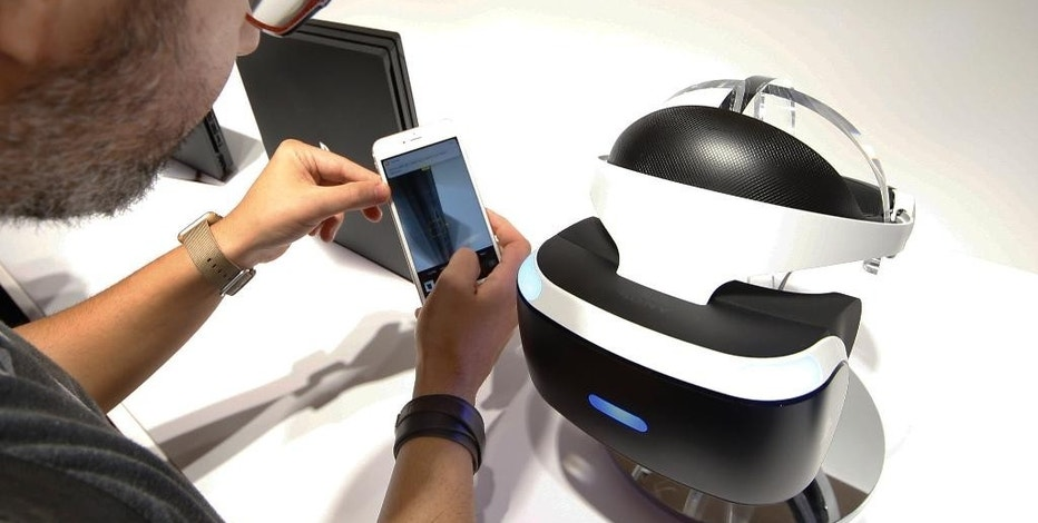 A visitor takes a photo of PlayStation VR headgear device during a PlayStation event in Tokyo, Tuesday, Sept. 13, 2016. Sony Corp.'s video game division is readying not just games but also music, movies and other kinds of entertainment for its Virtual Reality headgear, set to go on sale next month. The Japanese electronics and entertainment company's PlayStation VR headgear device, going on sale next month for about $400, less than rival VR headsets. (AP Photo/Shizuo Kambayashi)
