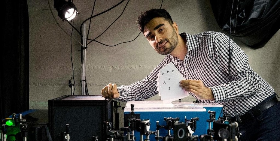 In this Monday, Sept. 12, 2016 photo, Barmak Heshmat poses with his prototype scanning device in a lab at Massachusetts Institute of Technology in Cambridge, Mass. Researchers at MIT have come up with a technology that can read the pages of a book without opening the cover, a development that could help museums better analyze antique books and ancient texts. (AP Photo/Michael Dwyer)