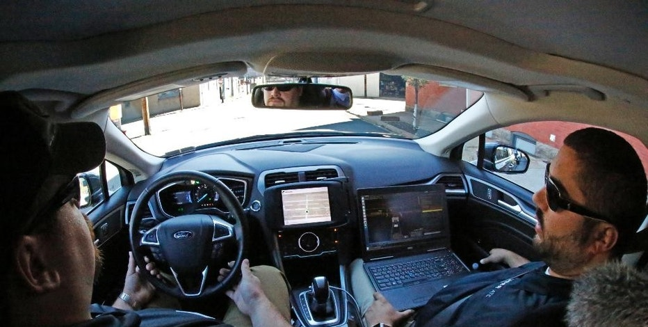 Uber safety driver Zachary Rearick, left, and vehicle operator Paul Rocchini take journalists on a drive through the streets of downtown Pittsburgh in a self driving Uber, Monday, Sept. 12, 2016. Starting Wednesday morning, Sept. 14, 2016 dozens of self-driving Ford Fusions will pick up riders who opted into a test program with Uber. While the vehicles are loaded with features that allow them to navigate on their own, an Uber engineer will sit in the driver's seat and seize control if things go awry. (AP Photo/Gene J. Puskar)