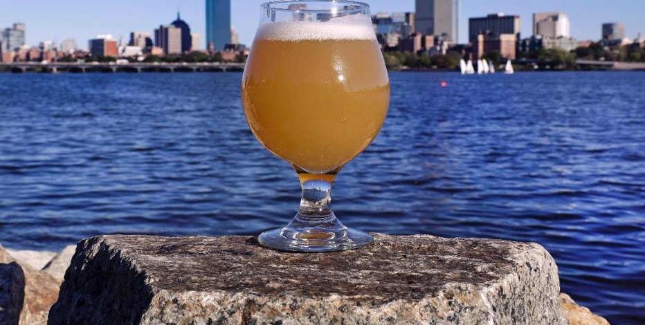 """A glass of Castle Island Brewing Company """"Chuck"""" beer, a dry hopped cream ale, rests on a rock along the bank of the Charles River, Thursday, Sept. 15, 2016, in Cambridge, Mass. Leading New England breweries are competing to see who can turn the questionable water of Boston's Charles River into the tastiest suds. (AP Photo/Charles Krupa)"""